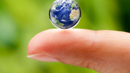 Finger with water droplet containing the world